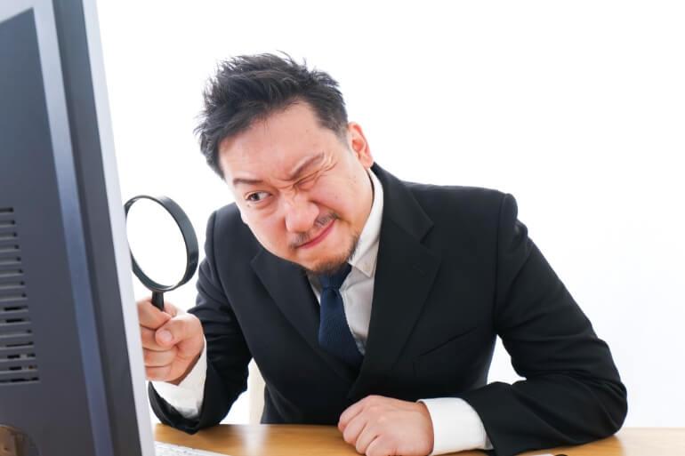 虫眼鏡でパソコンをのぞく男性
